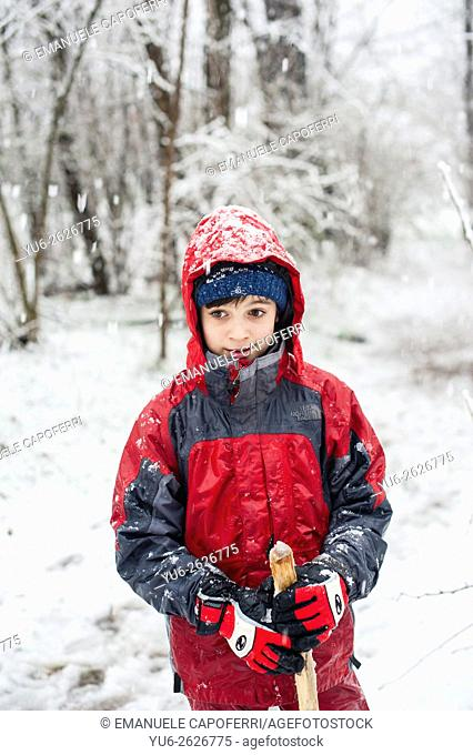 Child in the woods while snowing