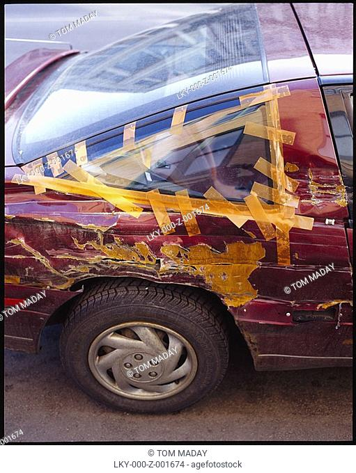 Beat up car held together with yellow tape