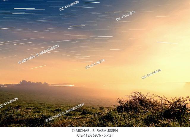 Meteor shower over tranquil landscape, Naestved, Denmark
