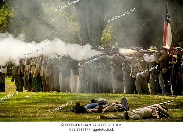 """Rifle-carrying """"""""Confederate"""""""" soldiers fire a volley at a Civil War battle reenactment in a Huntington Beach, CA, park. Note """"""""wounded"""""""" soldiers in foreground"""