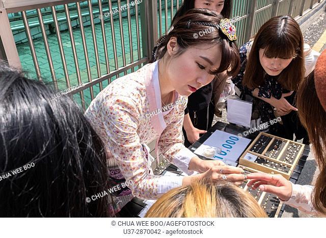 Female vendor selling rings in Jinhei, Korea