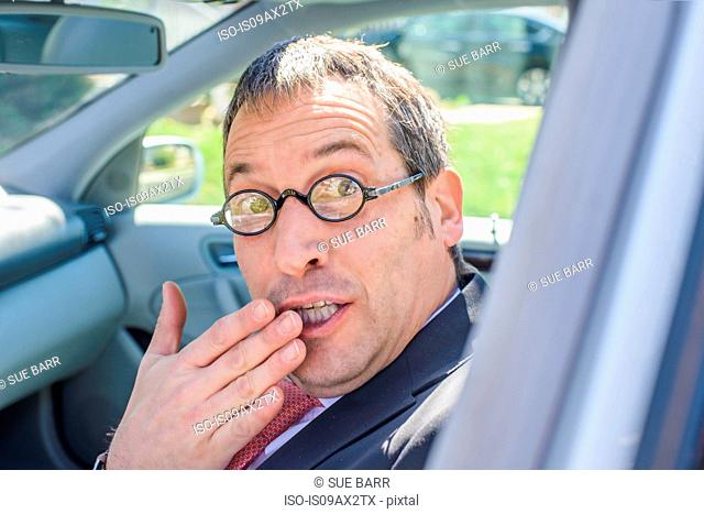 Man in car wearing eye glasses, hand over mouth looking at camera