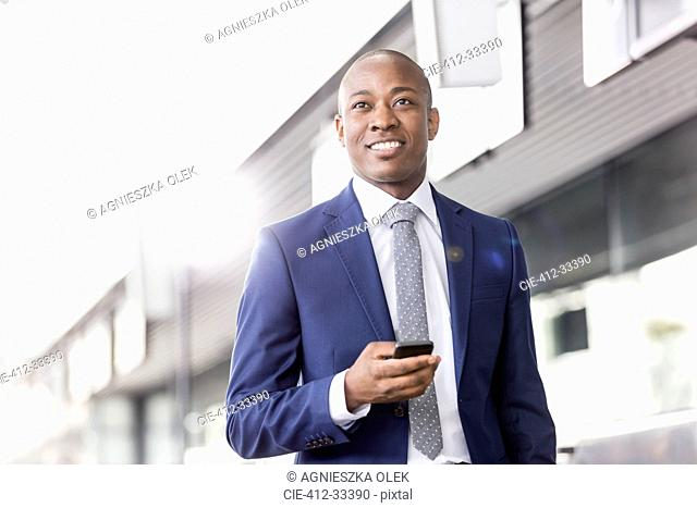 Smiling businessman with cell phone looking away