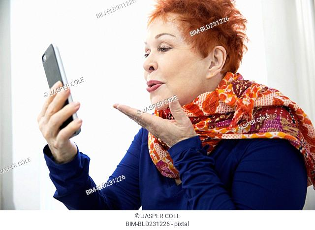 Older Caucasian woman blowing kiss at cell phone