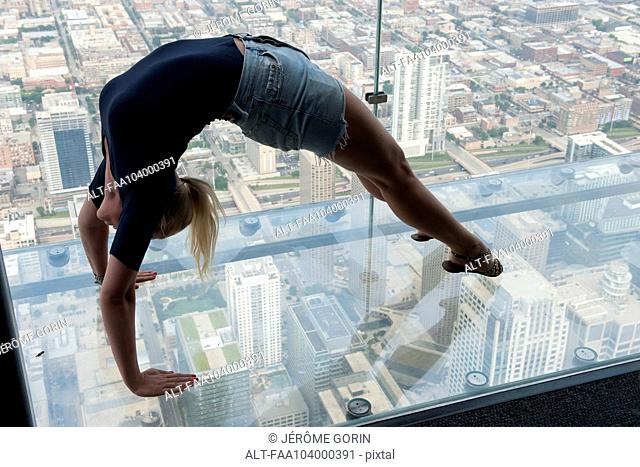 Woman doing backbend in glass-bottomed overservation deck at Willis Tower, Chicago, Illinois, USA