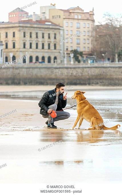Spain, Gijon, man talking with his dog on the beach