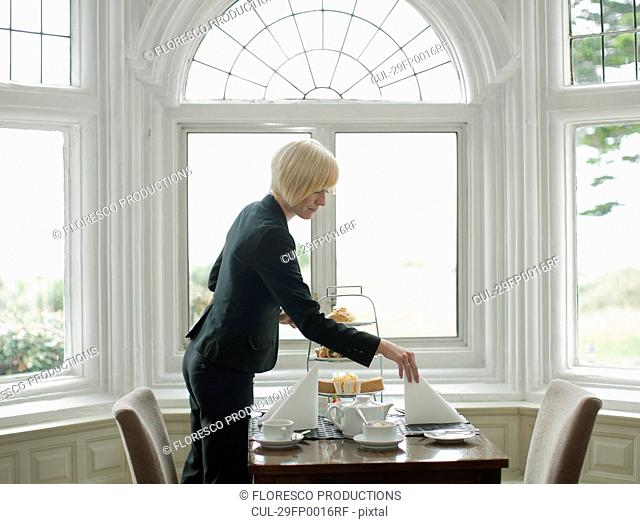 Woman setting up table