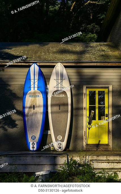Norfolk, Connecticut, USA A pair of windsurfing boards drying by the side of a house with a yellow door
