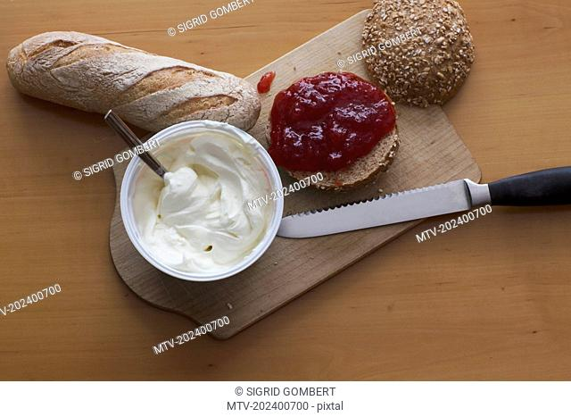 Fresh baguette, cheese, marmalade, bun on chopping board