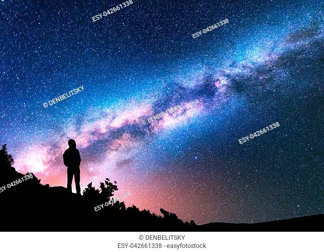 Silhouette of man with backpack on the hill against colorful Milky Way at night. Space background. Landscape with man, bright milky way, sky with stars