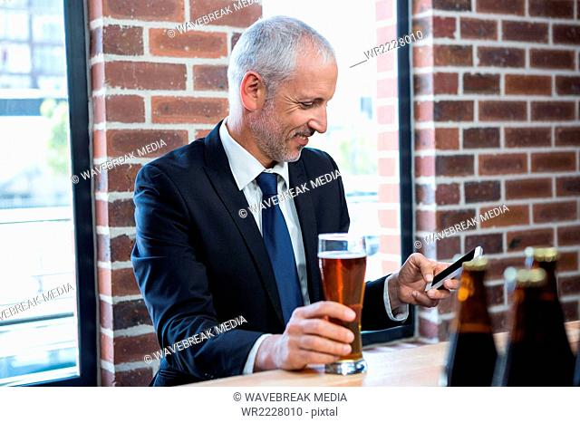 Businessman texting and holding a beer