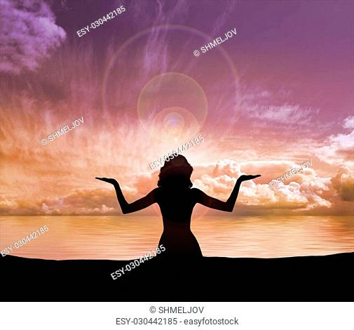 Sunset meditation. Silhouette of a woman doing yoga exercise in the evening
