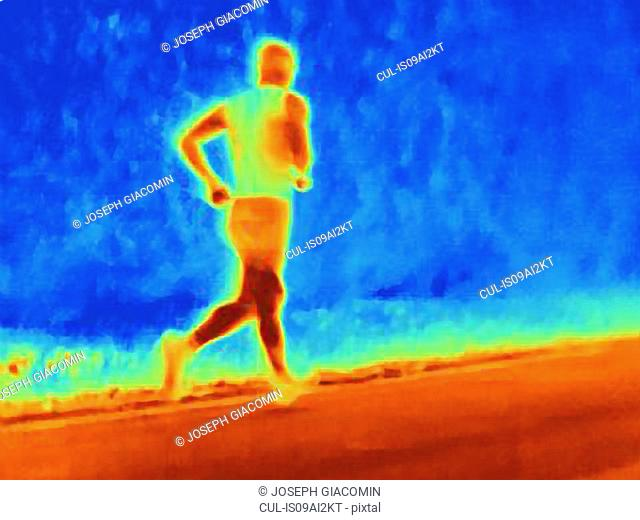 Rear view thermal photograph of young male athlete running. The image shows the heat of the muscles