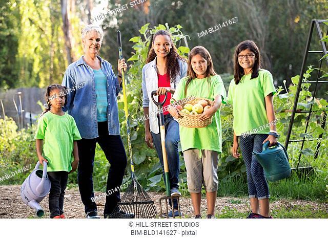 Women and children standing in vegetable garden