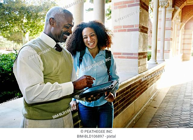 Professor with digital tablet talking to student