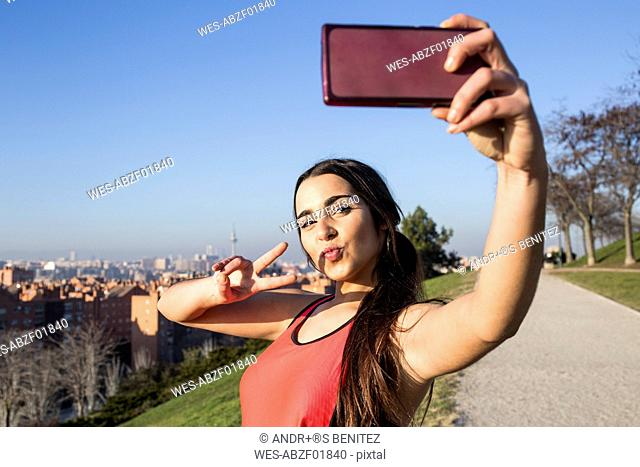 Female athlete posing for a selfie with her phone