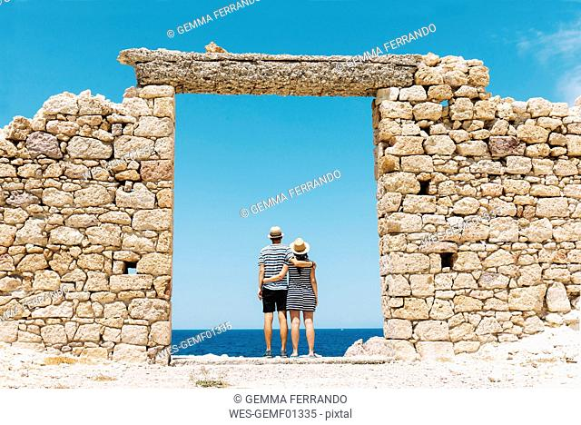 Greece, Milos, Firopotamos Beach, Couple standing in door in stone wall, looking at distance