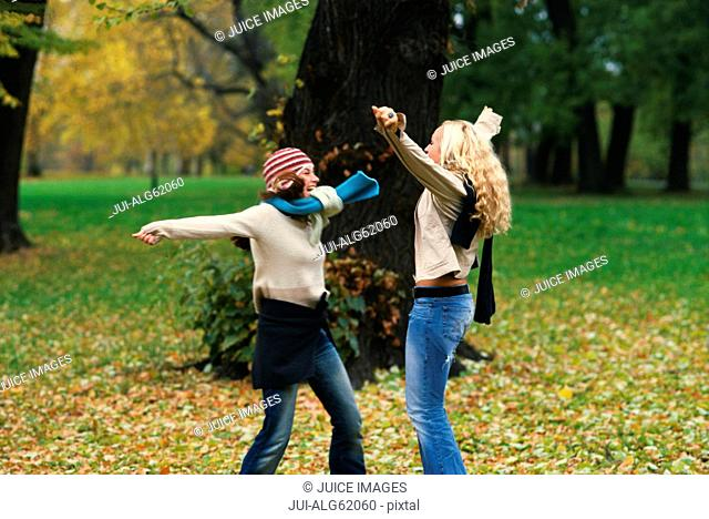 Young women greeting each other outdoors in Autumn