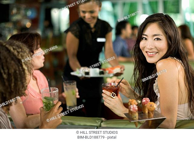 Multi-ethnic friends drinking cocktails and having sushi in nightclub