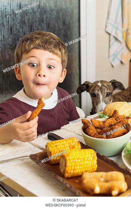 Boy with dog enjoying american food at dining table at home