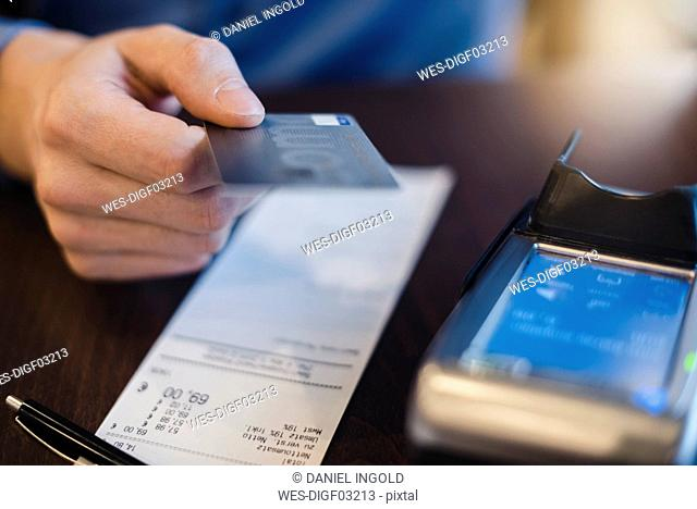 Customer paying bill with credit card, close-up
