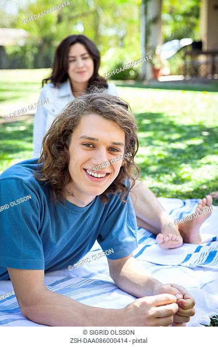 Man relaxing on picnic blanket with friend