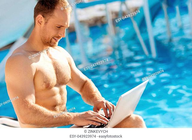 Work on vacation. Handsome well-built man wearing no shirt, sitting near a swimming pool and typing something on laptop