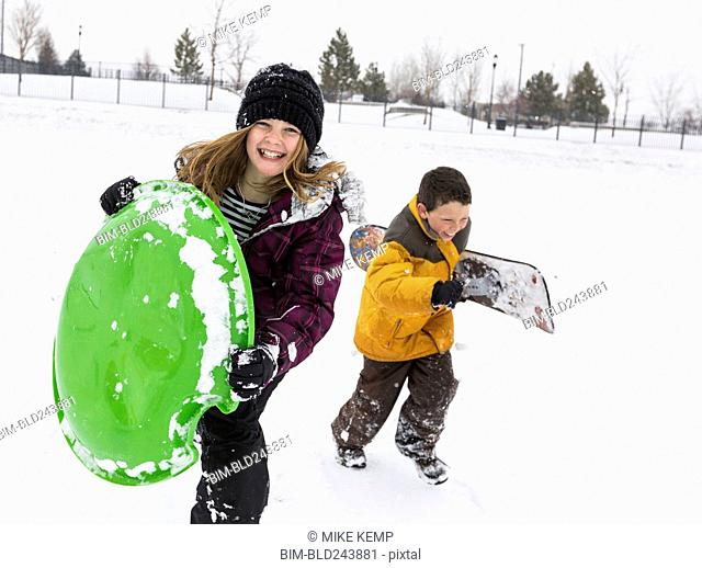 Smiling boy and girl carrying toboggan and snowboard in winter