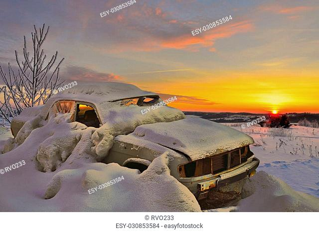 Old car in the snowy wilderness at sunset. Choose the right machine in extreme climates