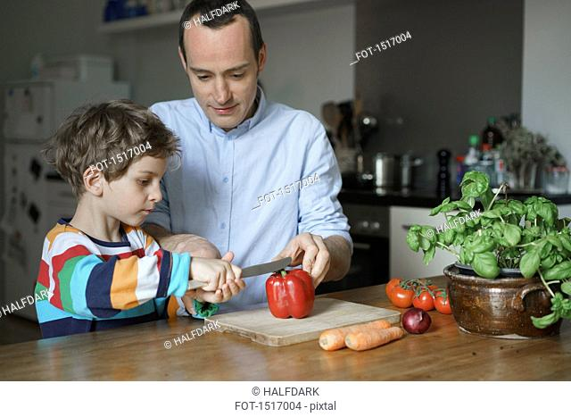 Father teaching son to cut vegetables at kitchen
