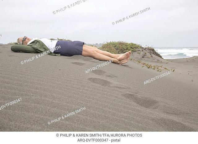 Woman relaxes on coastal dune, foggy day