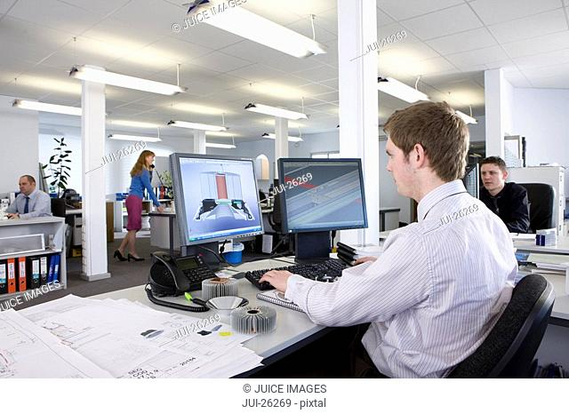 CAD designer working at computer monitors in office