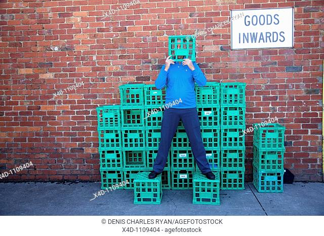 Man on crates, covering his face