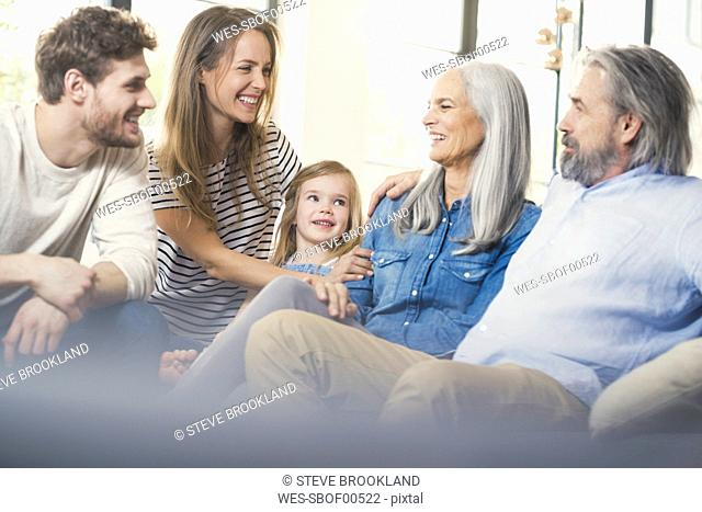 Extended family sitting on couch, smiling happily