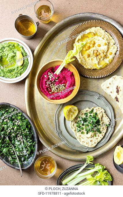 Various types of hummus with lettuce and unleavened bread