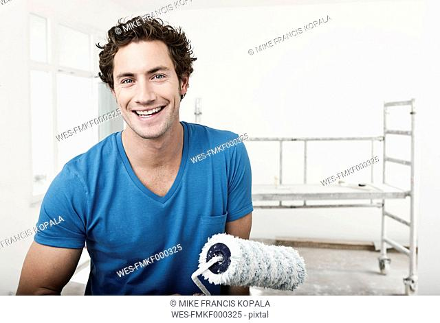 Germany, Cologne, Close up of young man holding paint roller in renovating apartment, portrait, smiling