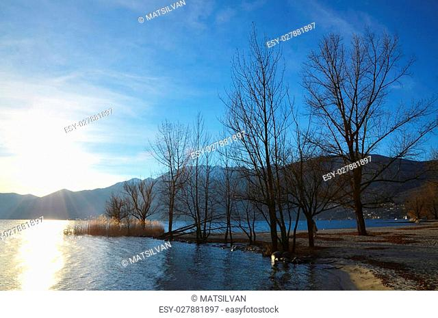 Sunlight over a lake with mountains and trees