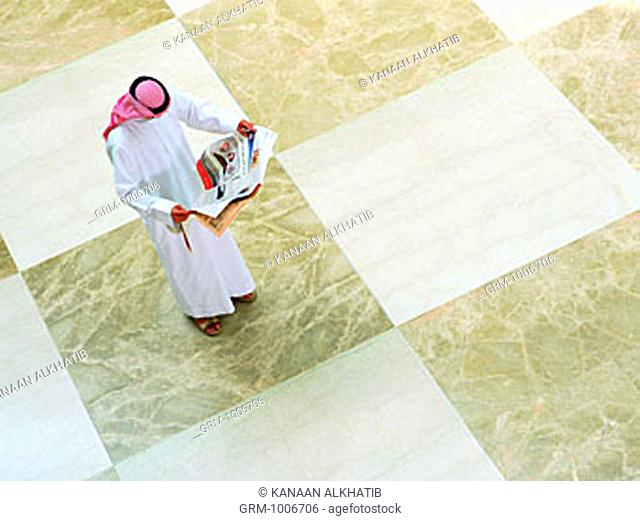 Arab man reading newspaper