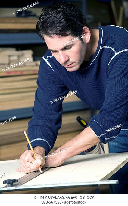 Man measuring a piece of wood with a straightedge