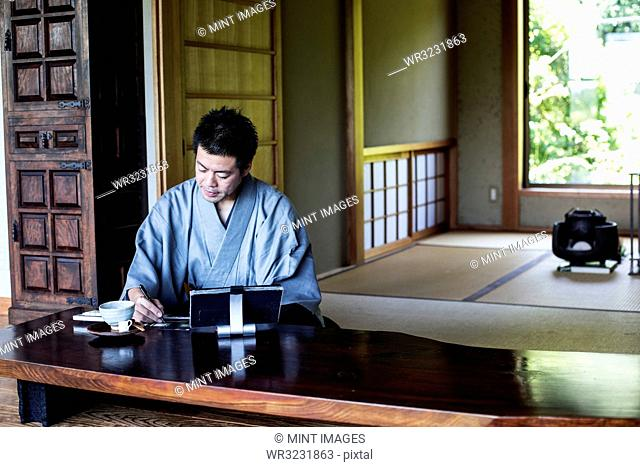Japanese man wearing kimono sitting on floor in traditional Japanese house, looking at digital tablet