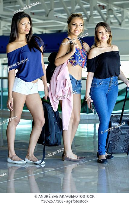 Three female teenagers with luggage at an airport terminal