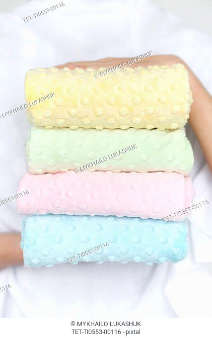 Hands of woman holding pastel color fabrics
