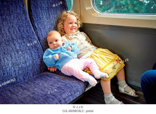 Female toddler sitting on train with baby sister