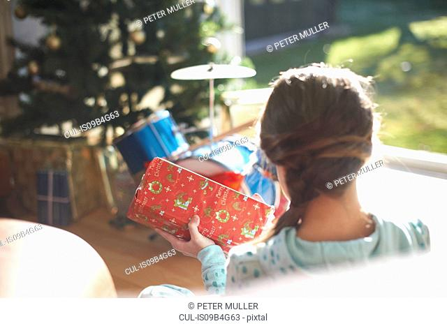 Over shoulder view of girl sitting on living room floor opening christmas gift