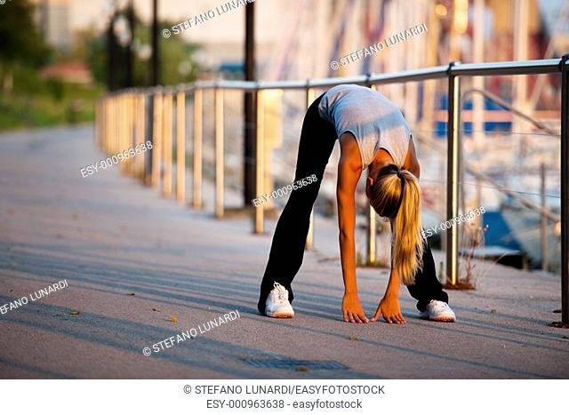 Young woman doing stretching before jogging