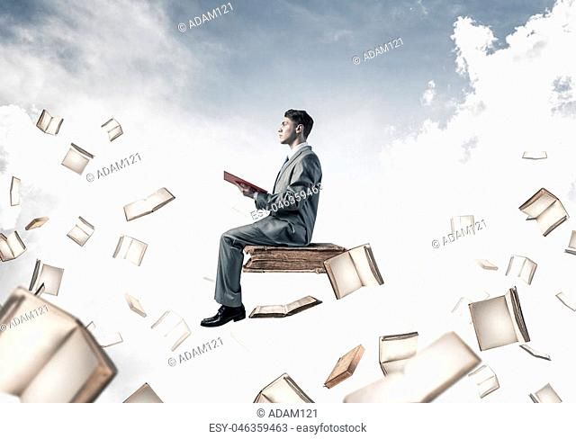 Young businessman floating in blue sky with red book in hands