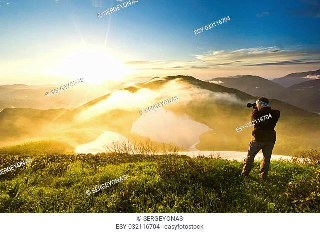 man with camera making photo on a hill at sunset and clouded sky