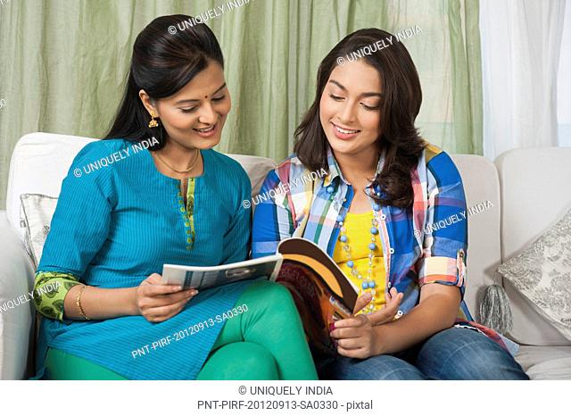 Two sisters reading a magazine and smiling