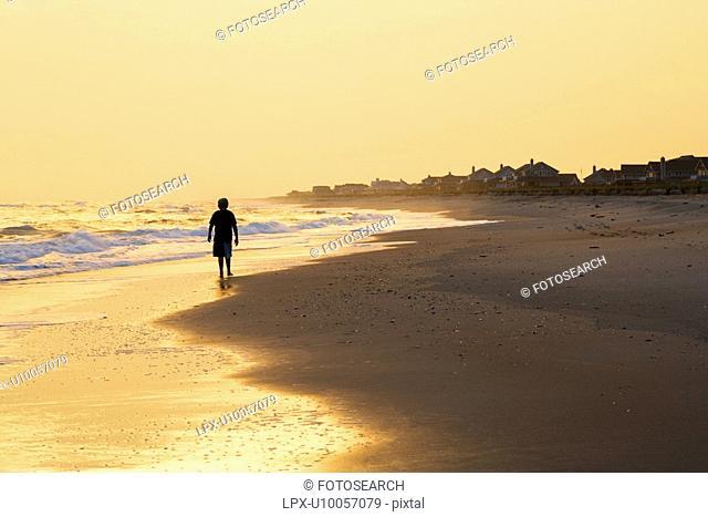 Caucasian pre-teen boy walking silhouette on beach at sunset