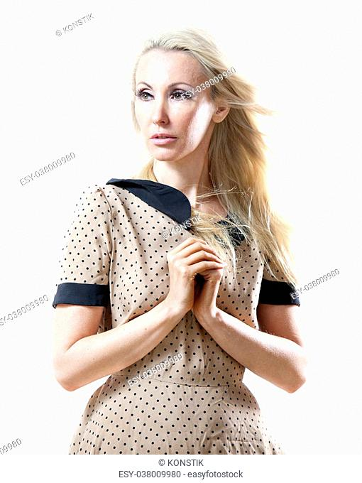 The beautiful thoughtful woman in a beige retro style dress with the fair long hair fluttering downwind